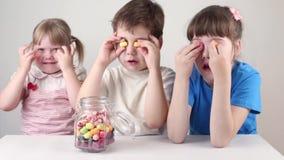Drei glückliches Kinderspiel mit Süßigkeiten nahe Glas auf Tabelle stock video