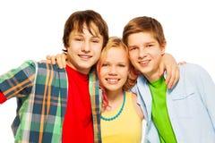 Drei glückliches Lächeln und Umarmen Teenagerlächeln Stockfotos