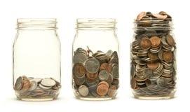 Drei Glasgläser, die Münzen anhalten Lizenzfreie Stockbilder