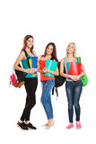 Drei glückliche Studenten, die zusammen mit Spaß stehen Stockfotografie