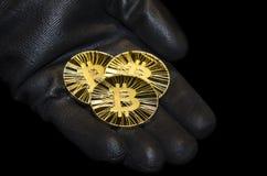 Drei goldene bitcoin Münzen auf schwarzen Handschuhen stockfoto