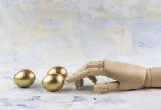 Drei goldene Eier berührt durch hölzernen Marionettenfinger gegen gemalte Wolken Stockfoto