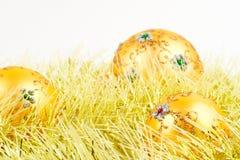 Drei goldene Weihnachtskugeln im gelben Filterstreifen stockbild