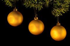 Drei goldene Weihnachtsverzierungen, die vom Baum hängen Stockfotografie