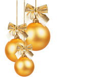 Drei Goldweihnachtsbälle mit goldenem Bogen Lizenzfreie Stockfotos