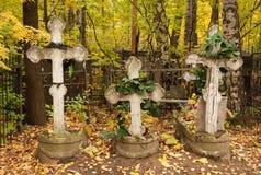 Drei Gräber mit den Kreuzen gebrechlich und Kränze am Kirchhof Lizenzfreies Stockfoto
