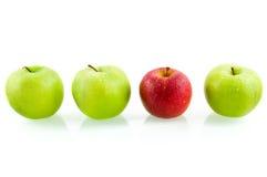 Drei grüne Äpfel mit einem roten Apfel Stockfotos