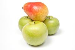 Drei grüne Äpfel und eine Birne Lizenzfreies Stockfoto