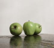 Drei grüne Äpfel und Reflexion auf hölzerner Beschaffenheit Lizenzfreie Stockfotos