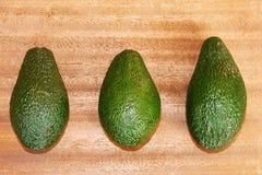 Drei grüne Avocados auf einem hölzernen Hintergrund Lizenzfreie Stockfotografie