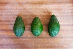 Drei grüne Avocados auf einem hölzernen Hintergrund Lizenzfreie Stockbilder