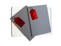 Drei graue Abdeckungsnotizbücher auf weißem Hintergrund, man ist unter 2 nahen Notizbüchern offen Lizenzfreie Stockbilder