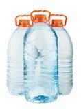 Drei große volle Plastikwasserflaschen mit orange Kappen Stockfotografie