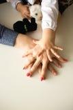 Drei Hände auf dem Tisch - Baby, Mutter und Vater Stockfoto