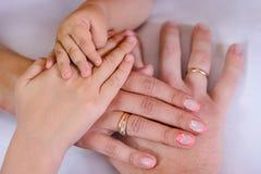 Drei Hände der Familie, des Kindes, der Mutter und des Vaters Das Konzept der Einheit, der Unterstützung, des Schutzes und des Gl Stockbilder