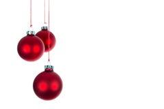Drei hängende Weihnachtsbälle an einem weißen Hintergrund Lizenzfreies Stockbild