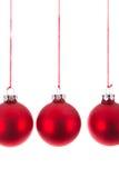 Drei hängende Weihnachtsbälle an einem weißen Hintergrund Stockfotografie