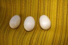 Drei hölzerne Eier, die auf einem Stoff liegen Stockbild