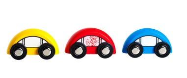 Drei hölzerne farbige Spielzeugautos Stockbilder