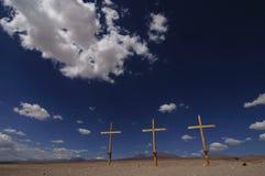 Drei hölzerne Kreuze in der Wüste mit blauem Himmel Lizenzfreies Stockfoto