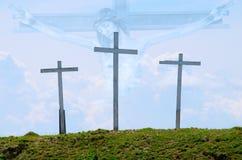 Drei hölzerne Kreuze mit Jesus im Hintergrund Stockfotos