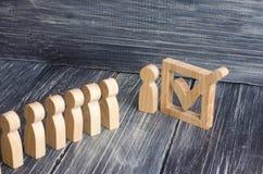 Drei hölzerne menschliche Figuren stehen zusammen nahe bei einer Zecke im Kasten Das Konzept von Wahlen und von Sozialtechnologie Stockbild