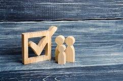 Drei hölzerne menschliche Figuren stehen zusammen nahe bei einer Zecke im Kasten Das Konzept von Wahlen und von Sozialtechnologie Lizenzfreie Stockfotografie