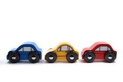 Drei hölzerne Spielzeugautos in einer Reihe Stockfotografie