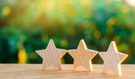 Drei hölzerne Sterne auf einem Hintergrund grünen bokeh Hintergrundes Das Konzept der Bewertung der Hotels und der Restaurants, d lizenzfreie stockbilder