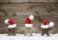 Drei hölzerne Sterne mit Sankt-Hüten auf hölzernem Hintergrund Lizenzfreie Stockfotografie