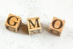 Drei hölzerne Würfel mit Buchstaben GMO steht für genetisch veränderten Organismus auf weißem Brett stockfoto