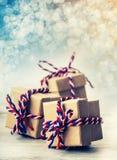 Drei handgemachte Geschenkboxen im glänzenden Farbweihnachtshintergrund Lizenzfreies Stockbild