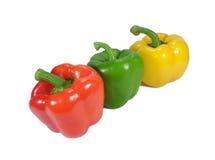 Drei helle Rote, grün, reifer grüner Pfeffer des Gelbs lokalisiert auf weißem Hintergrund Stockfotos