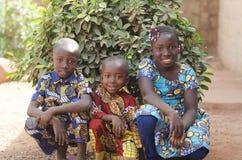 Drei herrliche afrikanische Kinder, die draußen lächeln und Laug aufwerfen stockfoto