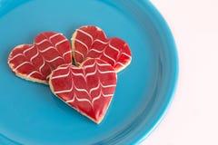 Drei Herz-geformte Plätzchen auf einer Platte Stockfotos