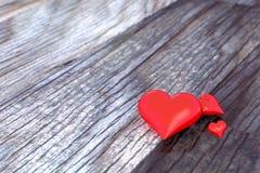 Drei Herzen auf einem Bretterboden Stockfotos