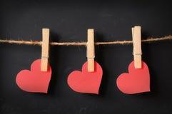 Drei Herzen, die an der Tafel hängen stockfotografie