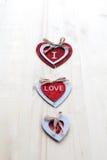 Drei Herzen mit Aufschriften der Liebe auf dem Hintergrund der Bretter ist nicht der Hintergrund des Schnees, Valentinsgruß ` s T Stockfotos