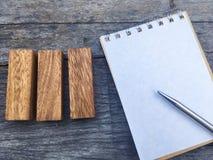 Drei Holzklotz neben Notizbuch und Stift für Projekt im Geschäft team Stockbilder
