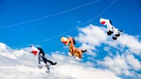 Drei Hund ähnliche Drachen, die auf den Himmel fliegen Stockbilder