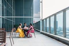 Drei indische Geschäftsleute, die während des Bruches bei der Arbeit sprechen Lizenzfreies Stockbild