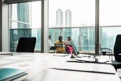 Drei indische Geschäftsleute, die während des Bruches bei der Arbeit sprechen Stockfoto