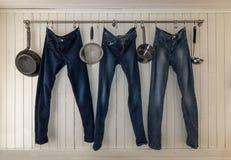 Drei Jeans, die an einer Küchenschiene hängen, um zu trocknen lizenzfreies stockbild