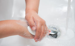 Kinderwaschende Hände mit Seife Stockbilder