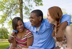 Drei Jugendfreunde, die draußen lachen Stockbilder