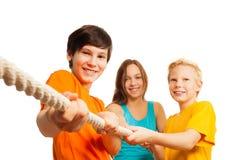 Drei jugendlich Freunde, die das Seil ziehen stockfotos