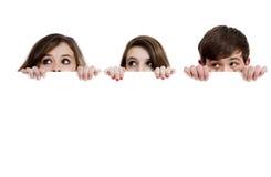 Drei Jugendliche, die über einen weißen Hintergrund spähen Stockfotos