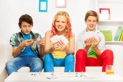 Drei Jugendliche, die Gesellschaftsspiel auf weißem Sofa spielen Lizenzfreie Stockfotografie