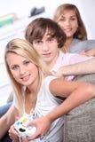 Drei Jugendliche, die Videospiele spielen Stockfotografie