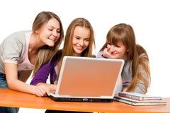 Drei Jugendlichmädchen, die das Netz surfen Lizenzfreies Stockfoto